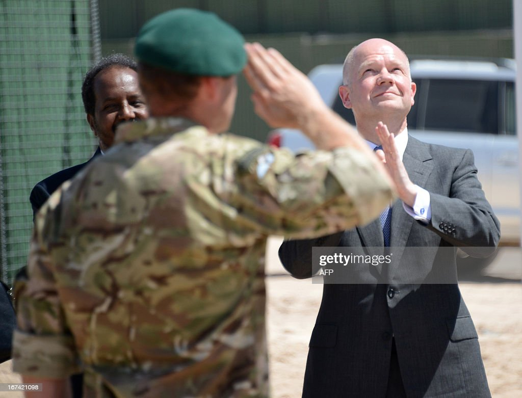 British Foreign Secretary William Hague (R), with Somali President Hassan Sheik Mohamud (L), look up as a British flag is raised in front of the newly opened British Embassy in Mogadishu on April 25, 2013. British Foreign Secretary William Hague opened a new embassy in Mogadishu on April 25, 22 years after London pulled its diplomats from conflict-torn Somalia. AFP PHOTO / Mohamed Abdiwahab