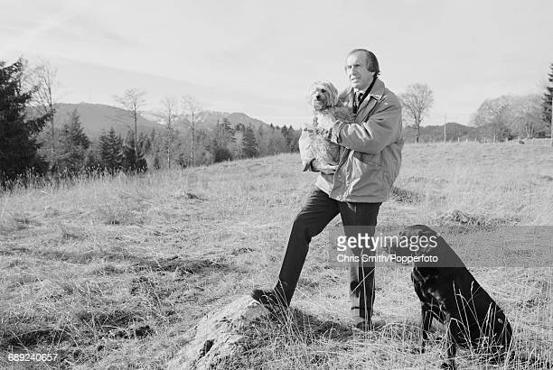 British former three time Formula One world champion racing driver Jackie Stewart pictured holding his Norfolk Terrier Boss with his pet Labrador dog...