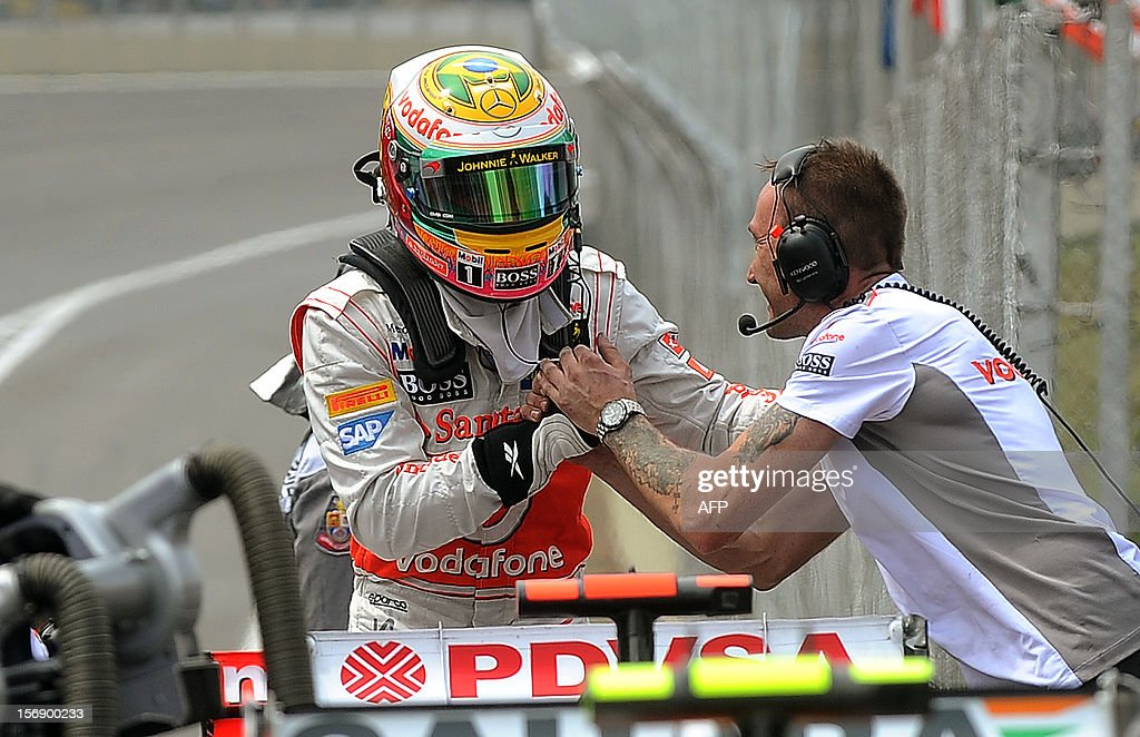 British Formula One driver Lewis Hamilton (L) celebrates with a McLaren team member his pole position for the Brazilian GP on Sunday, at the Interlagos racetrack in Sao Paulo, Brazil on November 24 , 2012 . AFP PHOTO