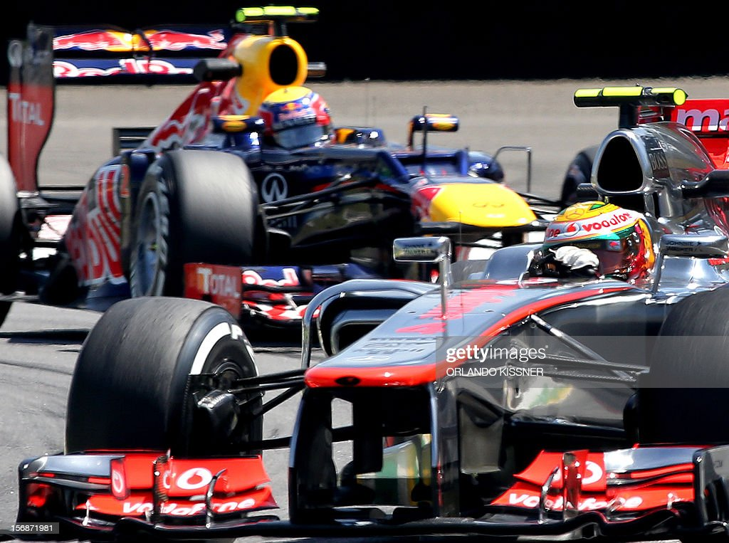 British Formula One driver Lewis Hamilton (front) negociates a turn followed by Australian Mark Webber during the second free practices on November 23, 2012 at the Interlagos speedway in Sao Paulo, Brazil. AFP PHOTO ORLANDO KISSNER