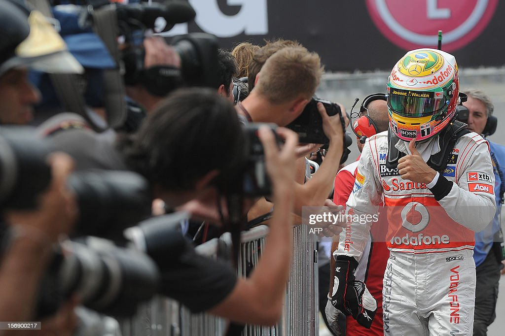 British Formula One driver Lewis Hamilton of McLaren gestures to celebrate the pole position for the Brazilian GP at the Interlagos racetrack in Sao Paulo, Brazil on November 24 , 2012. AFP PHOTO/NELSON ALMEIDA