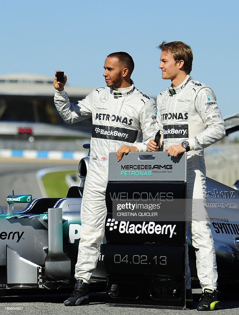 British Formula One driver Lewis Hamilton (L) takes pictures as he poses with his German teammate Nico Rosberg during the unveiling of the new Mercedes W04 as part of the Formula One training session at Jerez racetrack, on February 4, 2013 in Jerez de la Frontera. AFP PHOTO/ CRISTINA QUICLER