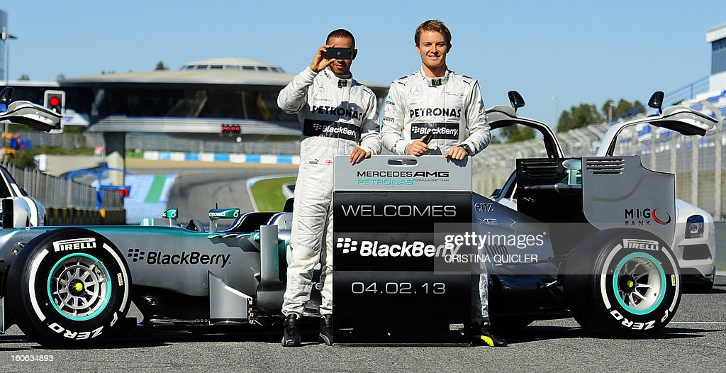 British Formula One driver Lewis Hamilton (L) takes pictures of photographers as he poses with his German teammate Nico Rosberg during the unveiling of the new Mercedes W04 as part of the Formula One training session at Jerez racetrack, on February 4, 2013 in Jerez de la Frontera.