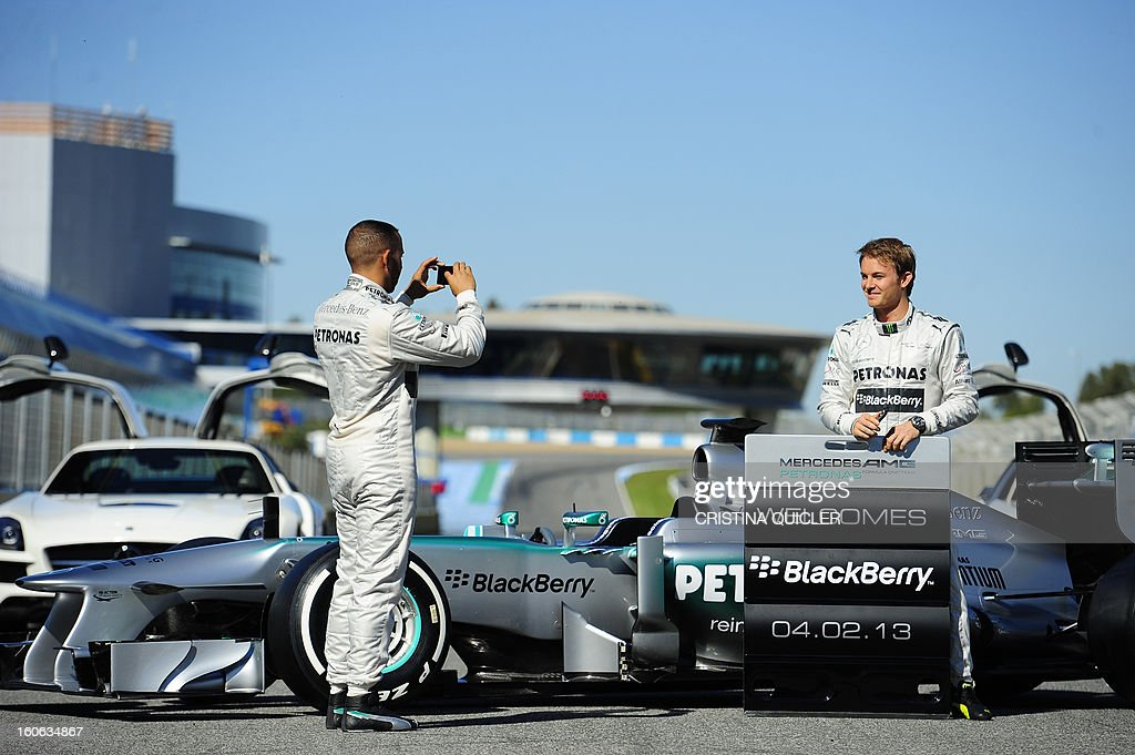 British Formula One driver Lewis Hamilton (L) takes pictures of his German teammate Nico Rosberg during the unveiling of the new Mercedes W04 as part of the Formula One training session at Jerez racetrack, on February 4, 2013 in Jerez de la Frontera. AFP PHOTO/ CRISTINA QUICLER
