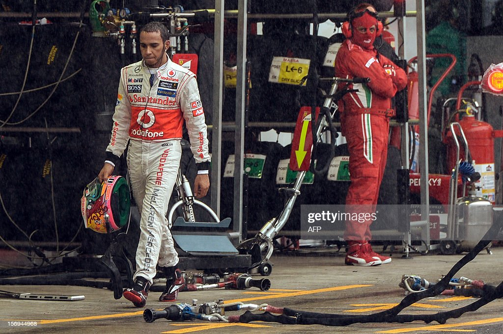 British Formula One driver Lewis Hamilton walks in the pits of Interlagos race track, on November 25, 2012 in Sao Paulo, Brazil. AFP PHOTO