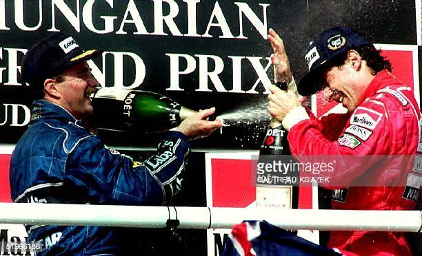 British FormulaOne driver Nigel Mansell sprays Brazilian driver Ayrton Senna with champagne 16 Aug during the podium ceremony of the Hungarian...