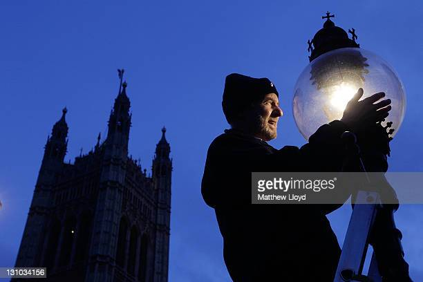 British Gas engineer Martin Caulfield services and cleans a gas lamp in front of Big Ben on October 31 2011 in London England Caulfield has been...
