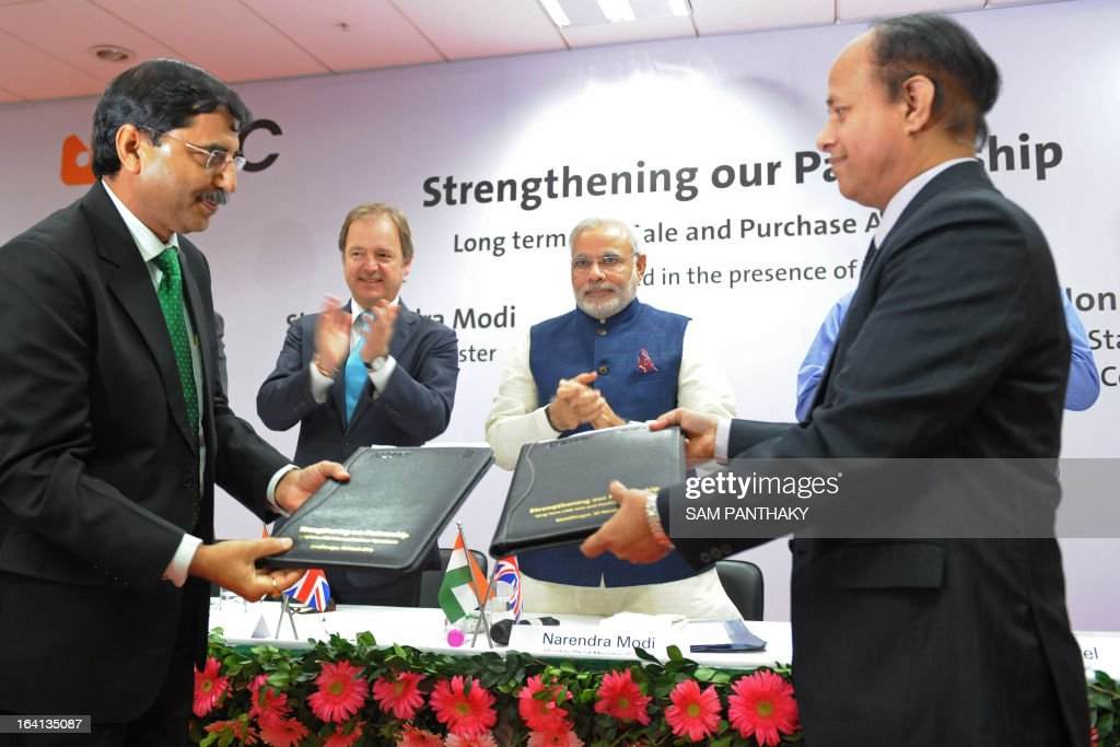 British Gas India's Managing Director and President Shaleen Sharma (L) and Gujarat State Petroleum Corporation Managing Director Tapan Ray (R) exchange documents during a memorandum of understanding signing ceremony in the presence of British Minister of State for Foreign Office Hugo Swire (2nd L) and Gujarat state Chief Minister Narendra Modi (2nd R) in Gandhinagar, some 30 kms. from Ahmedabad, on March 20, 2013. British Gas Group said March 20 it will supply up to 2.5 million tonnes per annum of liquefied natural gas to the state-owned Gujarat State Petroleum Corporation (GSPC) from 2015. AFP PHOTO / Sam PANTHAKY