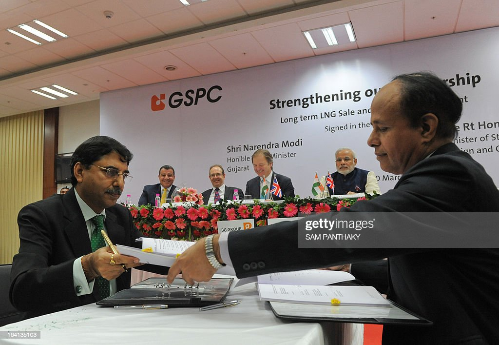 British Gas India's Managing Director and President Shaleen Sharma (L) and Gujarat State Petroleum Corporation Managing Director Tapan Ray (R) exchange documents during a memorandum of understanding signing ceremony in the presence of British Minister of State for Foreign Office Hugo Swire (C, background) and Gujarat state Chief Minister Narendra Modi (2nd R) in Gandhinagar, some 30 kms. from Ahmedabad, on March 20, 2013. British Gas Group said March 20 it will supply up to 2.5 million tonnes per annum of liquefied natural gas to the state-owned Gujarat State Petroleum Corporation (GSPC) from 2015. AFP PHOTO / Sam PANTHAKY