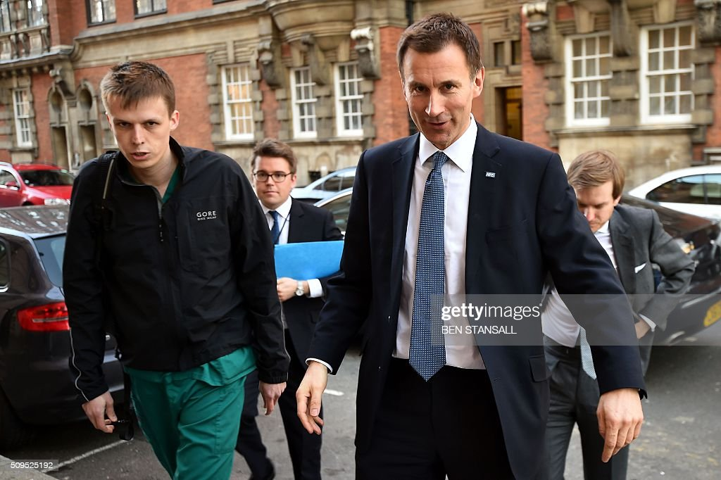 British Health Secretary Jeremy Hunt (R) arrives at Millbank studios with a man in medical scrubs (L) walking with him in central London on February 11, 2016. Britain's government said February 11 it would impose new contracts on junior doctors to force an end to strikes over changes to their working conditions. Health Secretary Jeremy Hunt told the House of Commons that the decision had been taken after negotiations with doctors' union the British Medical Association (BMA) failed. STANSALL