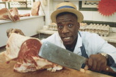 British heavyweight boxer Gary Mason poses with a meat cleaver in a butcher's shop circa 1990