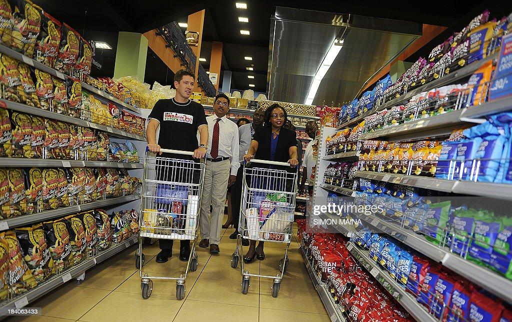 British High Commissioner to Kenya Christian Turner (L) accompanied by Kenya's Cabinet Secretary of East African Affairs, Commerce and Tourism Phyllis Kandie, pick goods at a shopping mall during a visit to show solidarity with shoppers on October 11, 2013, following recent terror attack by gunmen at the Westagate Mall, resulting in at least 72 deaths, and over 200 people were reportedly wounded.The attackers held hostages and later engaged in gun battles with Kenyan security forces.
