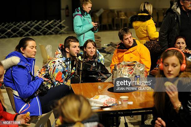 British holiday makers from Sheffield wait after spending the night and the day in a civic hall due to roads being blocked following heavy snowfall...