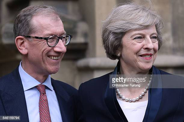 British Home Secretary Theresa May stands with her husband Philip John May before she makes a statement surrounded by members of the Tory party after...