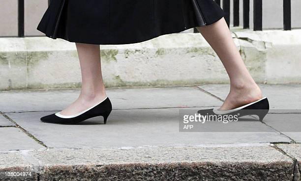 British Home Secretary Theresa May stops as the heal of her shoe gets stuck in a gap in the pavement as she arrives at number 10 Downing Street to...