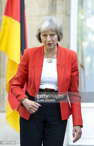 British Home Secretary Theresa May walks after a meeting with European Interior and Transport ministers in Paris on August 29 to discuss about new...