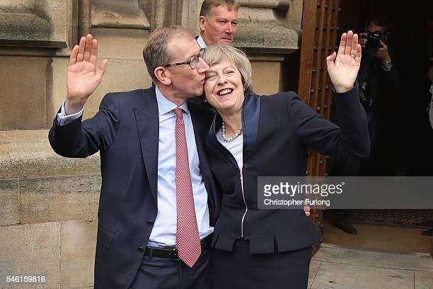 British Home Secretary Theresa May waves with her husband Philip John May as he kisses her head before she makes a statement after Andrea Leadsom...