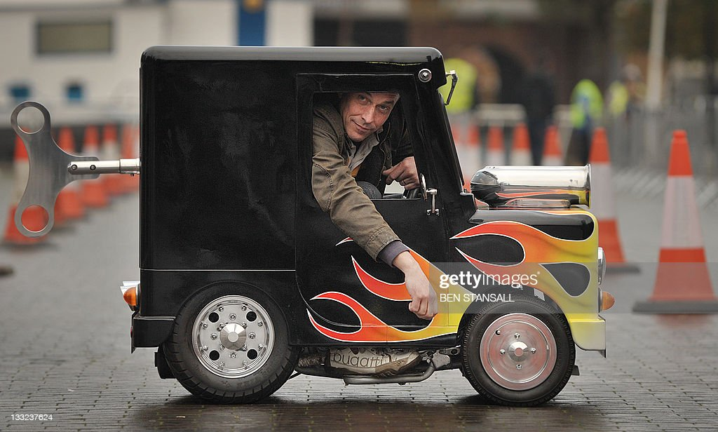British inventor of the world's smallest legally roadworthy car Perry Watkins sits in his vehicle measuring 104.14cm high, 66.04cm wide and 132.08cm long at Guinness World Records Day in London on November 17, 2011. Wacky Guinness world record holders got together to race their unlikely vehicles like the world's fastest toilet and smallest roadworthy car in London the mark the 7th annual Guinness World Records day.