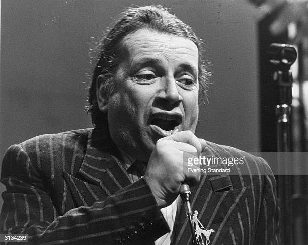 British jazz musician George Melly performing at Ronnie Scott's club in Frith Street London with his band the Feetwarmers