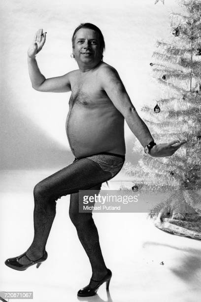 British jazz singer and writer George Melly pictured bare chested wearing fishnet stockings and high heeled shoes as he poses in front of a synthetic...