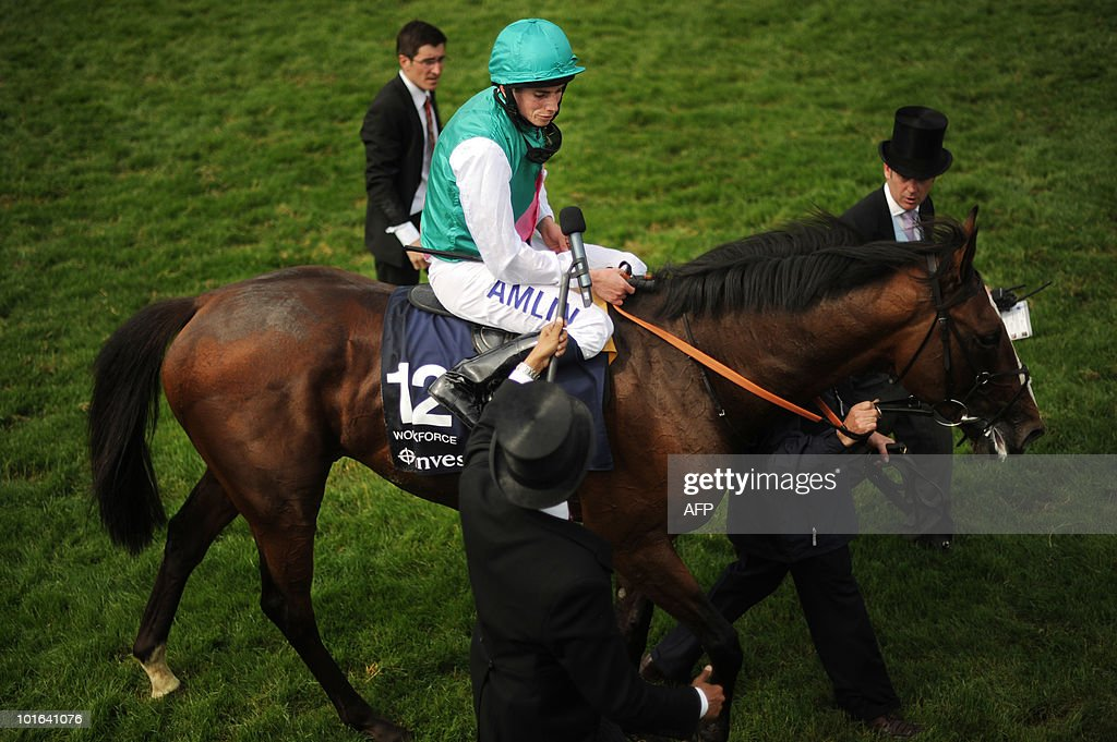 British jockey Ryan Moore (C) and horse Workforce are led from the racecourse after winning the Derby on the second day of the Epsom Derby, in Surrey, southern England, on June 5, 2010.