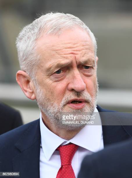 British Labour Party leader Jeremy Corbyn speaks to a journalist as he arrives for a meeting of the Party of European Socialists in Brussels on...