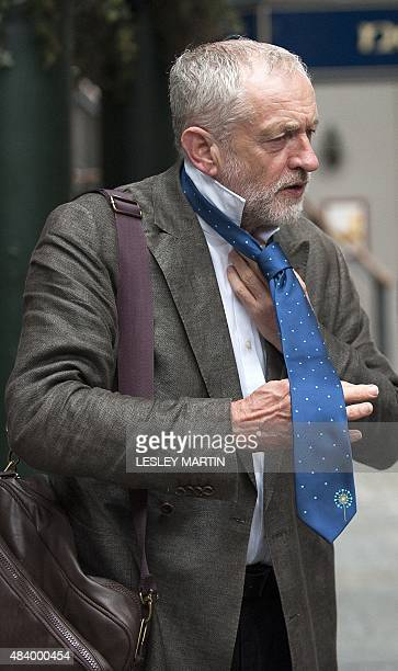 British Labour party leadership contender Jeremy Corbyn poses for pictures with a tie that he was given by a charity worker as he arrives to address...