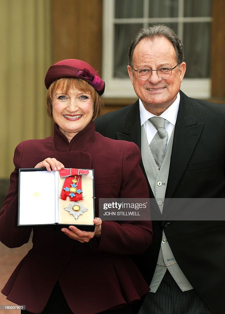 British Labour Party politician Tessa Jowell stands next to her husband David Mills as she poses for a picture with her Dame Commander of the Order of the British Empire (DBE) insignia after it was presented to her by the Prince of Wales during the Investiture ceremony at Buckingham Palace in central London on January 25, 2013. AFP PHOTO/POOL/JOHN STILLWELL