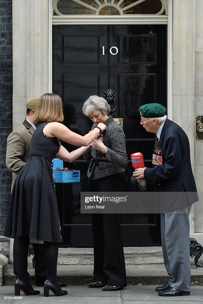 British Legion Director of Communications Claire Rowcliffe (2L) assists British Prime Minister Theresa May (2R) with her poppy as they take part in a photocall for this years 'Poppy Appeal' with veterans Stewart Harris (L) and Roy Miller (R) at Downing Street on October 31, 2016 in London, England. This year, The Royal British Legion is asking the nation to 'Rethink Remembrance' by recognising the sacrifices made not just by the Armed Forces of the past, but by today's generation too.