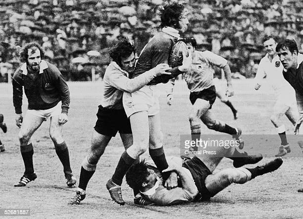 British Lions full back J P R Williams is pinioned by New South Wales half back John Hipwell and prop John Howard with Delme Thomas and John Taylor...