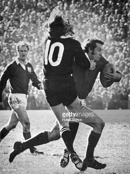 British Lions scrum half Gareth Edwards fends off New Zealand All Black back Bob Burgess during the third rugby test match at Wellington 31st July...