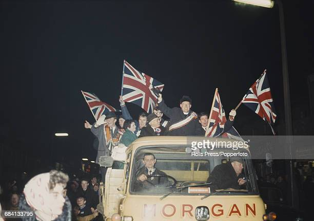 British loyalist politician religious leader and leader of the Protestant Unionist Party Ian Paisley pictured standing with supporters waving union...