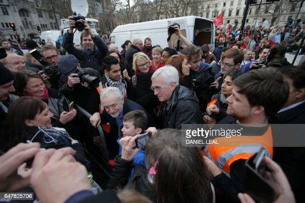British main opposition Labour Party leader Jeremy Corbyn and the shadow chancellor of the exchequer John McDonnell pose for a picture with a child...