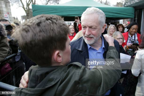 British main opposition Labour Party leader Jeremy Corbyn embraces a supporter as he attends a rally against private companies' involvement in the...