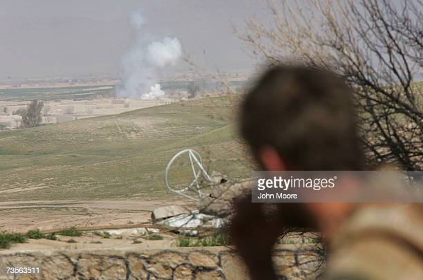 British Marine looks on as British mortars explode to provide a smoke screen during a military operation near the Kajaki hydroelectric dam March 13...