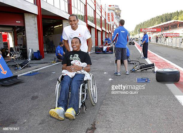 British McLarenMercedes driver Lewis Hamilton walks in the pits of the SpaFrancorchamps racetrack with his brother Nick 13 September 2007 in Spa...