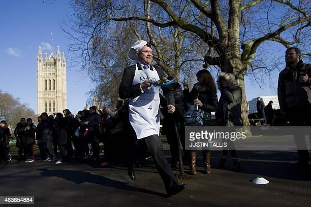 British member of parliament Andrew Rosindell runs with his frying pan and pancake as he takes part in the annual charity parliamentary pancake race...