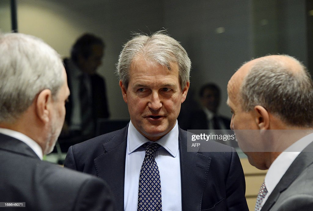 British Minister for Agriculture Owen Paterson speaks with unidentified officials prior to the start of the Agriculture and Fisheries Council meeting...