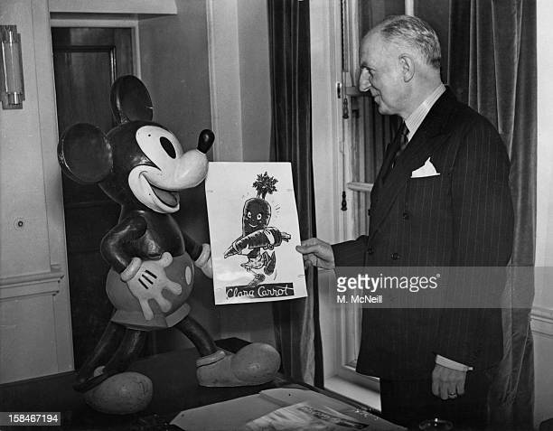 British Minister of Food Frederick Marquis with a cartoon and a figure of Mickey Mouse sent by the Walt Disney Studios to help with the ministry's...