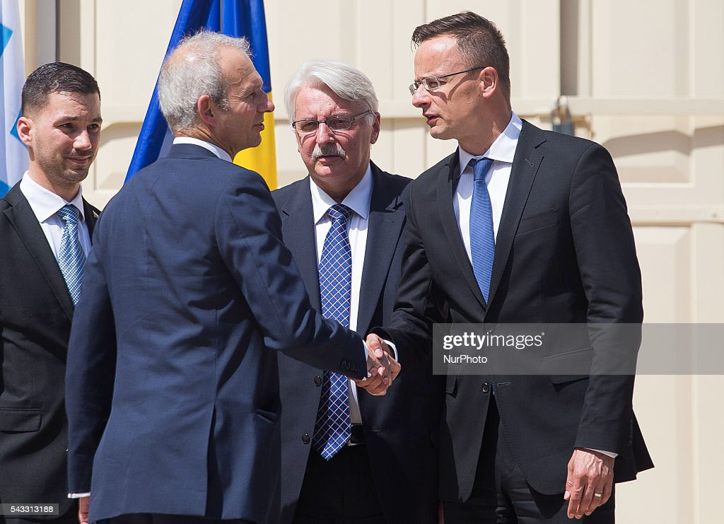 British Minister of State for Europe David Lidington, second left, shakes hands with Hungarian Foreign Minister Peter Szijjatro, as Polish Foreign Minister Witold Waszczykowski, second right, and Slovakian Foreign Ministry State Secretary Lukas Parizek, left, stand next to them during a break in talks, in Warsaw, 27 June, 2016, Poalnd