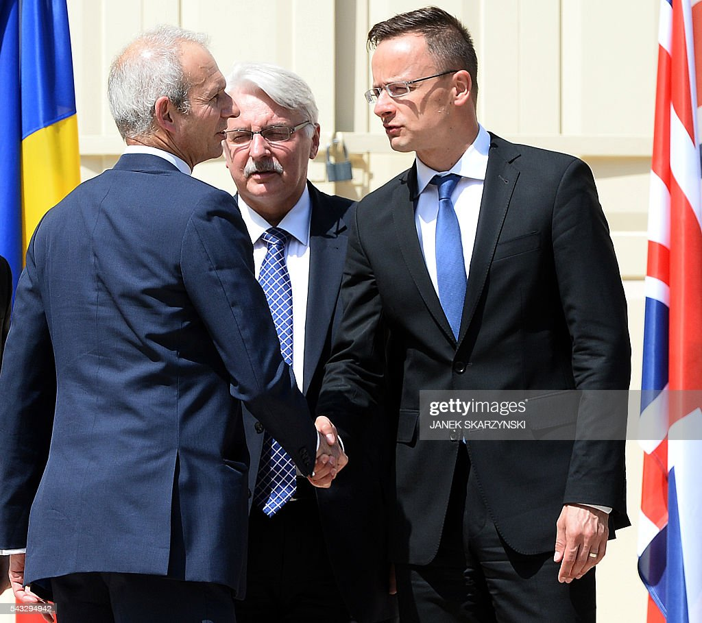 British Minister of State for Europe David Lidington (L) shakes hands with Hungarian Foreign Minister Peter Szijjatro (R) next to Polish Foreign Minister Witold Waszczykowski during a break in talks in Warsaw, Poland on June 27, 2016. / AFP / JANEK