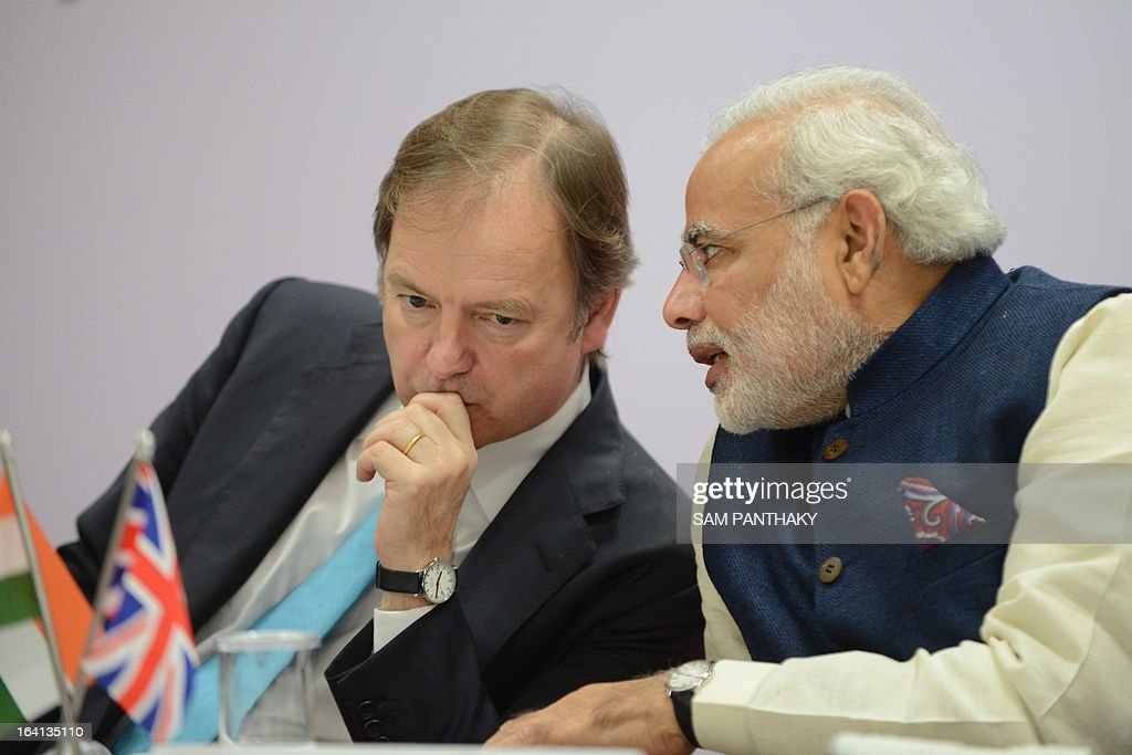 British Minister of State for Foreign Office Hugo Swire (L) listens to India's Gujarat state Chief Minister Narendra Modi during a signing ceremony between British Gas and Gujarat State Petroleum Corporation in Gandhinagar, some 30 kms. from Ahmedabad, on March 20, 2013. British Gas Group said March 20 it will supply up to 2.5 million tonnes per annum of liquefied natural gas to the state-owned Gujarat State Petroleum Corporation (GSPC) from 2015. AFP PHOTO / Sam PANTHAKY