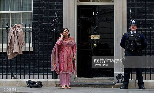 British Minister Without Portfolio and Chairman of the Conservative Party Baroness Sayeeda Warsi poses for pictures after hanging her coat on the...