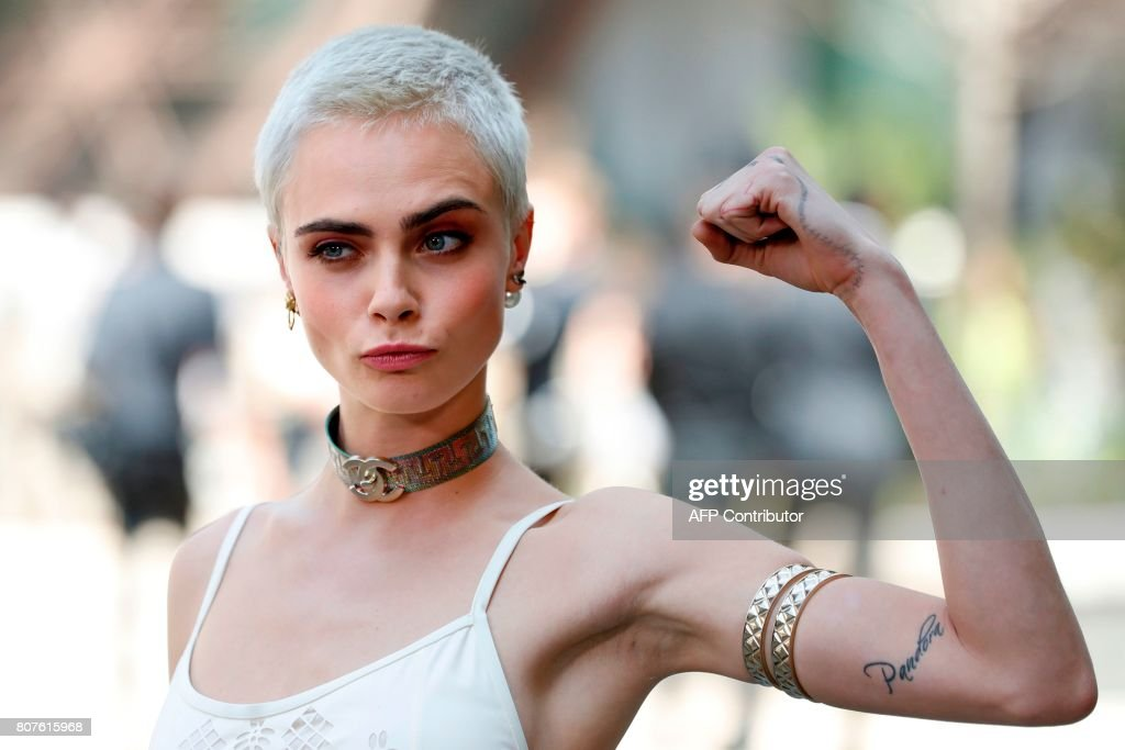 British model and actress Cara Delevingne poses during the photocall before Chanel 2017-2018 fall/winter Haute Couture collection show in Paris on July 4, 2017. / AFP PHOTO / Patrick KOVARIK
