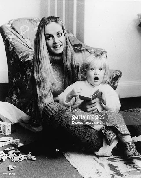 British model and actress Twiggy wears a turtleneck and leg warmers as she sits on the floor and holds her daughter Carly Lawson on her lap...