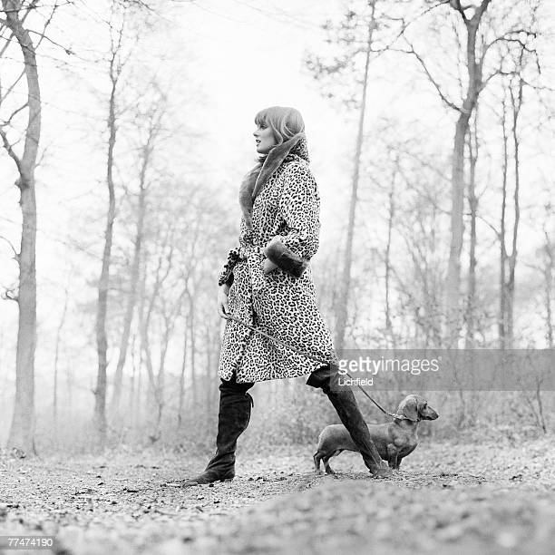 British model and former Fashion Editor of British Vogue Grace Coddington walking a dachshund in woods in Marlow Buckinghamshire on 18th March 1964
