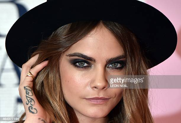 British model Cara Delevingne poses on the red carpet to attend the BRIT Awards 2015 in London on February 25 2015 AFP PHOTO / LEON NEAL RESTRICTED...