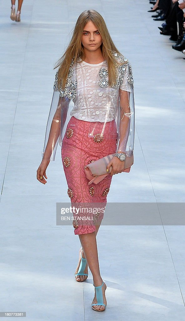British model Cara Delevingne presents a creation by Burberry Prorsum during the 2014 Spring/Summer London Fashion Week in London on September 16, 2013.