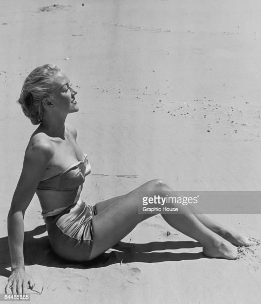British model Elizabeth Chantler sunbathing on a beach in Sussex circa 1955