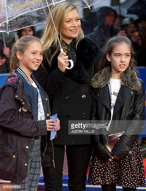 British model Kate Moss poses for pictures on the red carpet with her daughter Lila Grace and an unidentified guest upon their arrival for the world...